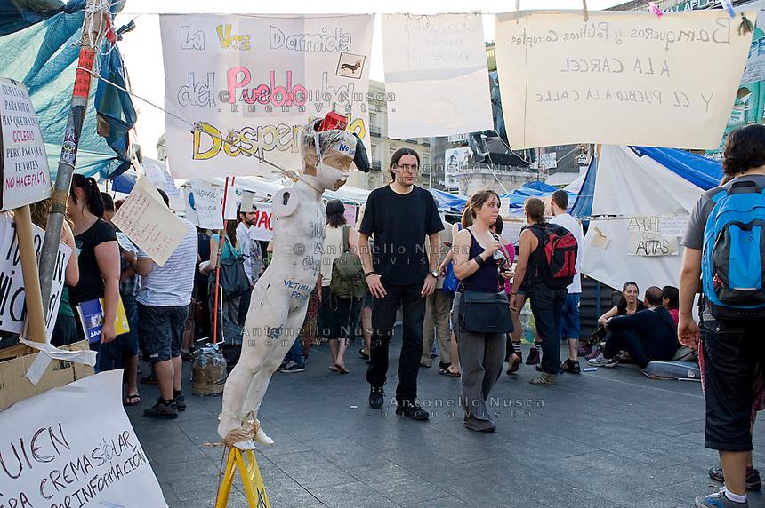 """People walk past a sign reading, """"The voice of the people has awakened"""", at Madrid's Puerta del Sol..Un manichino con un cartello con la scritta """"La voce del popolo si è svegliata"""", nella tendopoli di Plaza del Sol a Madrid"""