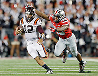 Virginia Tech Hokies quarterback Michael Brewer (12) gets away from Ohio State Buckeyes linebacker Darron Lee (43) during the 1st quarter of their game in Ohio Stadium on September 6, 2014.  (Dispatch photo by Kyle Robertson)