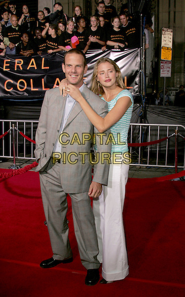 """PETER BERG & ESTELLA WARREN.The Los Angeles Premiere of """"Collateral"""" held at The historic Orpheum Theatre in Downtown Los Angeles, California .August 2,2004.full length, gry, grey suit, green and white stripes, hug, embrace, gesture.www.capitalpictures.com.sales@capitalpictures.com.Supplied By Capital Pictures"""