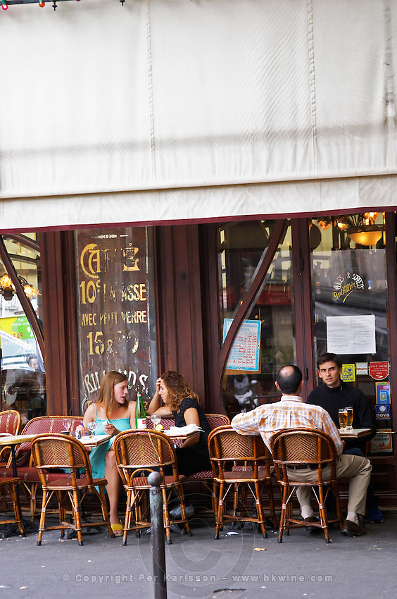 Le Bistrot du Peintre cafe bar terrase outside seating on the sidewalk. Two young women having a drink and chatting on a wicker sofa and two young men in chairs with glasses of beer The Bistrot du Peintre is an old fashioned Paris café cafe bar restaurant of art nouveau design with polished brass, mirrors and old signs