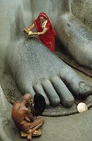 INDIA, Shravana Belagola, Karnataka, granite feet of Jain statue Bahubali, woman with sari pouring water and praying naked Jain monk / INDIEN Karnataka, Jain Glaeubige und nackter Moench beim Gebet am Jainheiligtum Bahubali eine 17 Meter hohe Statue aus Granit des Jain Heiligen Lord Bahubali oder Gommata oder Gomateshvara in Shravana Belagola , Jains praktizieren als oberstes Gebot Gewaltverzicht ahimsa und sind strikte Vegetarier und lehnen das Kastensystem ab - Religion Jainismus als Reformbewegung aus Hinduismus hervorgegangen