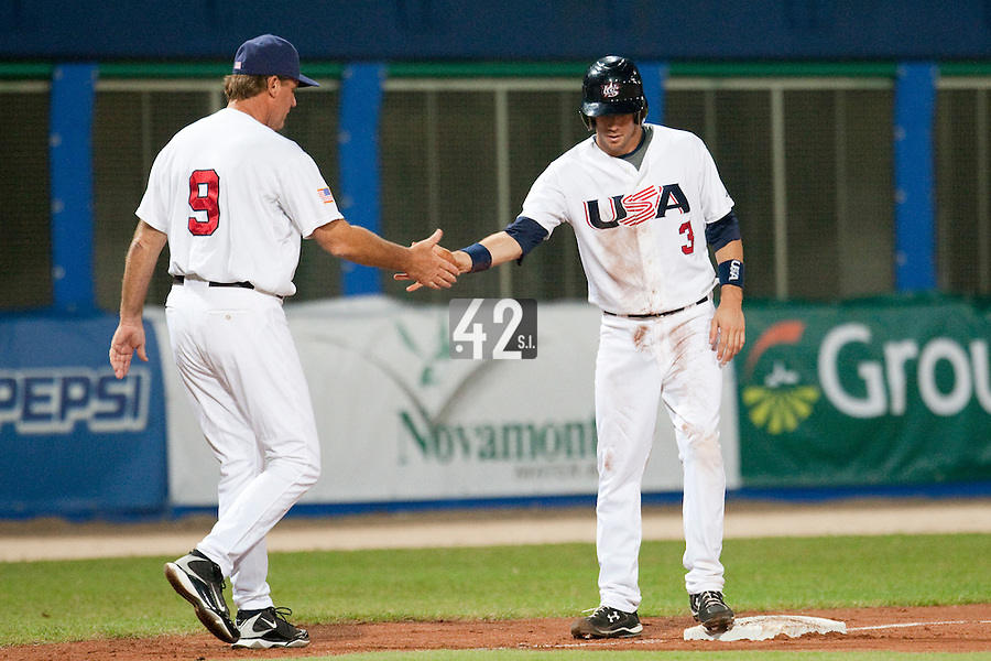 24 September 2009: Trevor Plouffe of Team USA is congratulated by third base coach Jamie Quirk during the 2009 Baseball World Cup final round match won 5-3 by Team USA over Cuba, in Nettuno, Italy.