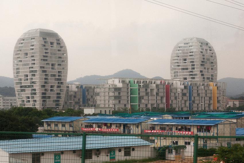 Une ville-nouvelle dans l'un des districts de Zhongshan (ville préfécture qui administre 18 villes périphériques, 5 millions d'habitants au total). Au premier plan les inévitables baraquemements où logent les ouvriers migrants qui ont construit cette région et aujourd'hui acceptent de moins en moins leurs conditions de travail.