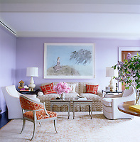 The walls of the living room are painted a soft lilac and this corner is furnished with a comfortable contemporary seating arrangement