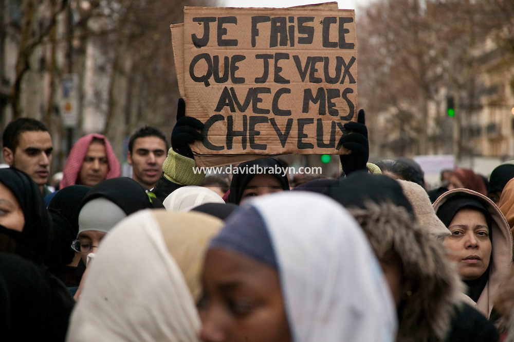 "A woman wearing a head scarf holds up a sign in French that reads ""I'll do what I want with my hair"" during a street protest held in Paris, France, 21 December 2003, against a law that plans to restrict the wearing of veils in public schools."
