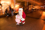 Santa Claus working the crowds at Sutter Creek's annual Parade of Lights Christmas parade downtown on a rainy night in the  Mother Lode of Calif.