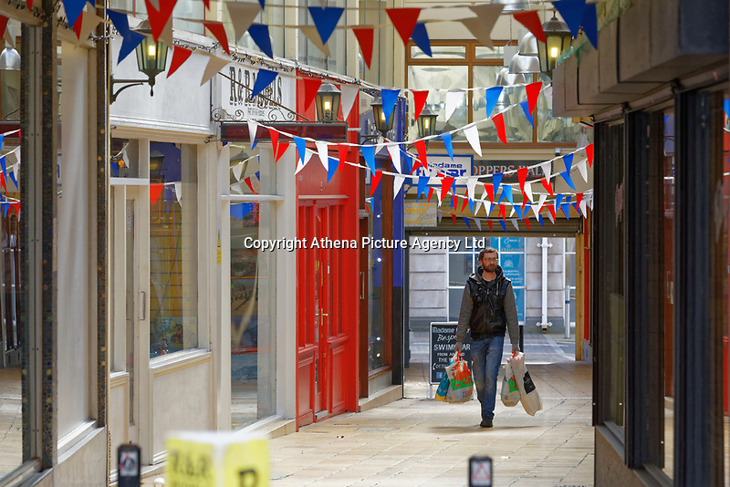 Pictured: A man carries shopping bags as he walks through Shopper's Walk arcade in Swansea, Wales, UK. Saturday 21 March 2020<br /> Re: Covid-19 Coronavirus pandemic, UK.