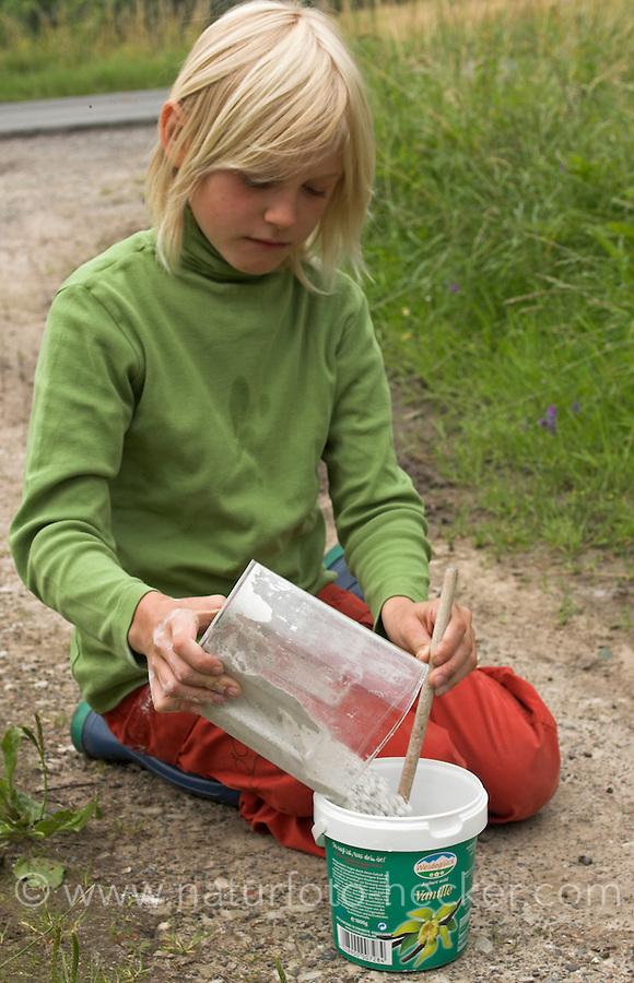 Kinder gießen Tierspur aus Gips, Junge hat Gips abgemessen und füllt diesen zum Gipsanrühren in alten Becher