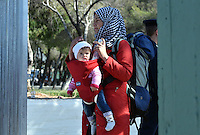 Pictured: A migrant mother with her young child at the fence of the refugee camp Tuesday 23 February 2016<br /> Re: Migrants at a refugee camp in the Schisto area of Athens, Greece.