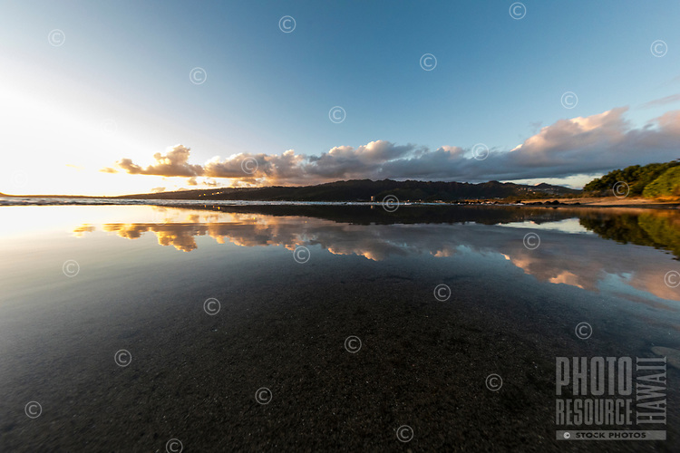 Tidal pools reflect sunset's glow over land, ocean and sky near Koko Head, East O'ahu.