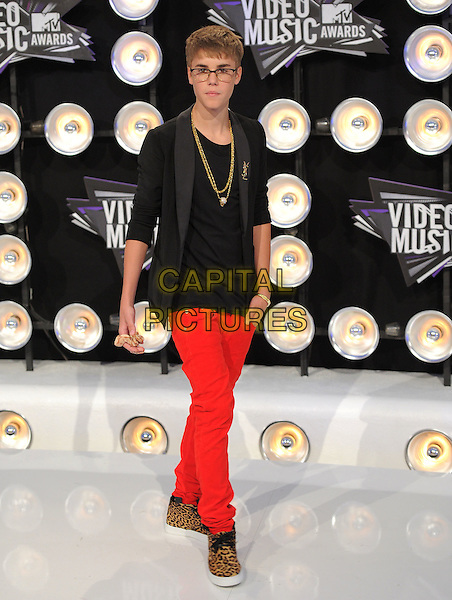 Justin Bieber .Arrivals  at the 2011 MTV Video Music Awards held at Nokia Theatre L.A. Live in Los Angeles, California, USA..28th August 2011.full length black blazer jacket top gold necklaces glasses ysl Yves Saint Laurent red jeans denim brown leopard print sneakers trainers shoes.CAP/RKE/DVS.©DVS/RockinExposures/Capital Pictures.