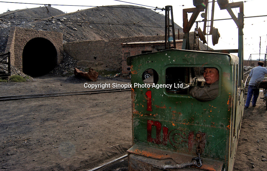 Coal mining worker outside the underground coal mine field in Wu Hai Xi, Inner Mongolia, China..