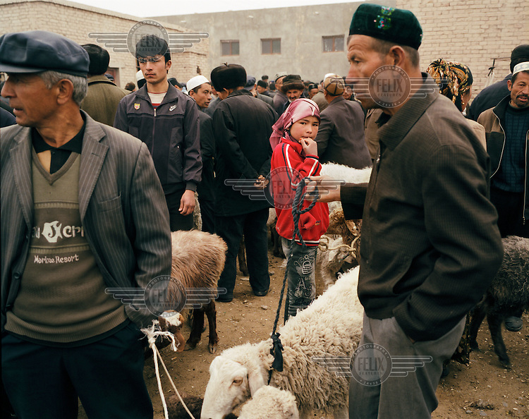 A young girl walks through the sheep market. Uighur (Uyghur) farmers trade their cattle at the Sunday market in Artux. For centuries the oasis towns of Xinjiang were used as stopping points along the Silk Road, leaving the region with a unique cultural legacy..