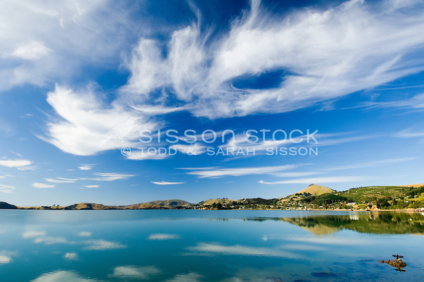 Dramatic cloud formations and reflected in the calm waters of Otago harbour Broad Bay on Otago Peninsula near Dunedin.