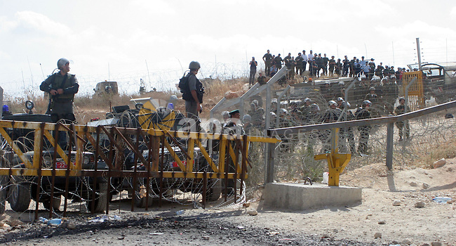 Israeli soldiers watch the  Palestinians celebration  near Israel's controversial separation wall near the West Bank village of Bilin. Palestinians celebrated a ruling by Israel's Supreme Court that a part of the controversial separation barrier near Bilin must be rerouted.