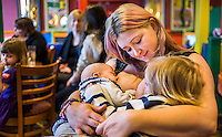 A mother tandem feeds her two children, one about twelve weeks old and one about 28 months old, at a sling meet held in the family restaurant and play area in a pub.
