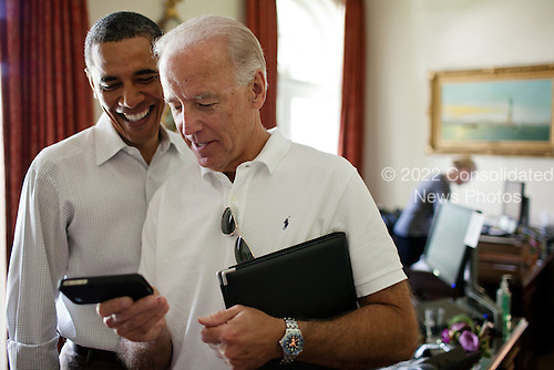 United States Vice President Joe Biden and U.S. President Barack Obama look at an app on an iPhone in the Outer Oval Office, Saturday, July 16, 2011. .Mandatory Credit: Pete Souza - White House via CNP