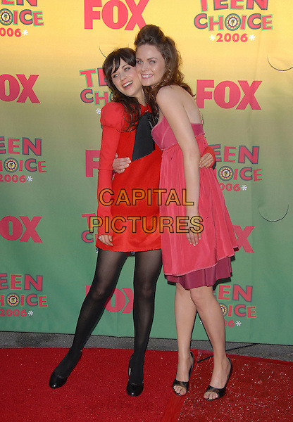 ZOOEY DESCHANEL & EMILY DESCHANEL.At The 2006 Teen Choice Awards - Arrivals, .held at The Universal Ampitheatre in Universal City, California, USA, August 20th 2006..full length sisters family siblings red dress black tights puff sleeves bow pink.Ref: DVS.www.capitalpictures.com.sales@capitalpictures.com.©Debbie VanStory/Capital Pictures