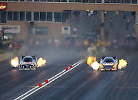 Jul. 18, 2014; Morrison, CO, USA; NHRA funny car driver Ron Capps (right) races alongside Courtney Force during qualifying for the Mile High Nationals at Bandimere Speedway. Mandatory Credit: Mark J. Rebilas-