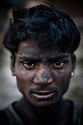 Miner in Jharia mines, Tinku Bhuia poses for a portrait in Bokapahari in Jharia, Jharkhand, India. The miners work for 9-10 hours a day and make Rs.150 ($3.5) a day loading the coal trucks in the BCCL coal mines in Jharia. Coal fires rage just below the surface of the ground, making it too hot to walk with naked feet, noxious gases spew up from fissures, making the environment toxic. Photo: Sanjit Das