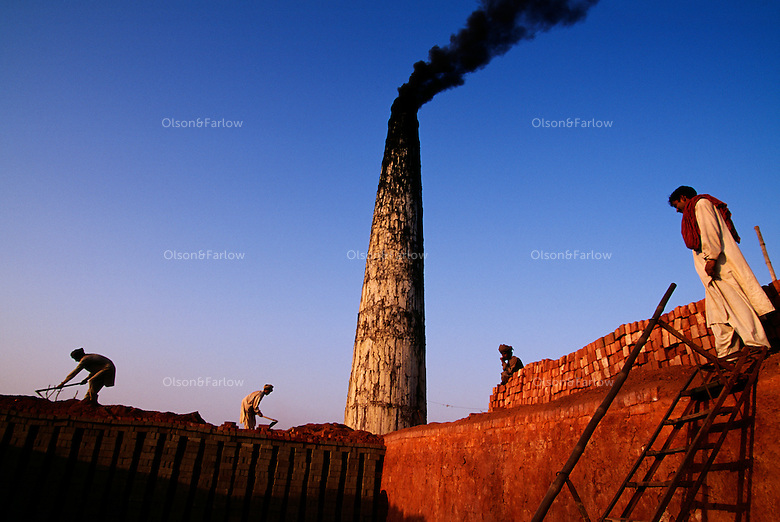 Smoke pours from a stack as men work stacking bricks that are made at this factory in a rural area.<br /> <br /> Just outside the Harappa site they are making bricks the same way the ancient Harappans did, by burying clay bricks and burning rice husks for fuel to fire the bricks.
