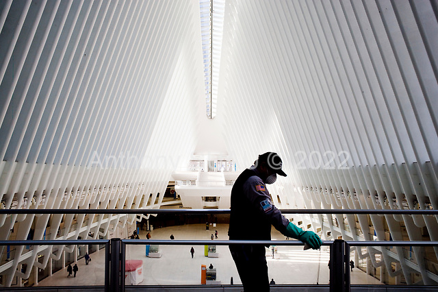 New York, New York<br /> March 20, 2020<br /> 3:38 PM<br /> <br /> Manhattan under the coronavirus pandemic. <br /> <br /> A worker cleans the public rails that overlook the interior of the Oculus, a terminal station on the PATH system, within the World Trade Center complex in the Financial District of Manhattan.<br /> <br /> Normally this space would be filled of people.
