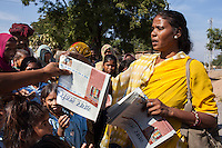 Shanti Adivasi (in yellow saree), 52, sells a few copies of this week's newspapers to villagers in Manikpur, Chitrakoot, Uttar Pradesh, India on 6th December 2012. Shanti used to be a wood gatherer, working with her parents since she was 3, and later carrying up to 100 kg of wood walking 12km from the dry jungle hills to her home to repack the wood which sold for 3 rupees per kg. After learning to read and write in an 8 month welfare course, at age 32, she became a reporter, joining Khabar Lahariya newspaper since its establishment in 2002, and making about 9000 rupees per month, supporting her family of 14 as the sole breadwinner. Photo by Suzanne Lee for Marie Claire France.