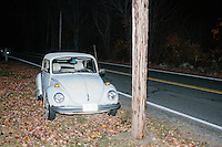 An old Volkswagen Beetle car stands parked next to the road while Republican presidential candidate and former Florida governor Jeb Bush speaks to a crowd in the barn of Dr. and Mrs. James Betti in Rye, New Hampshire, for former Massachusetts senator Scott Brown's No B.S. BBQ series.