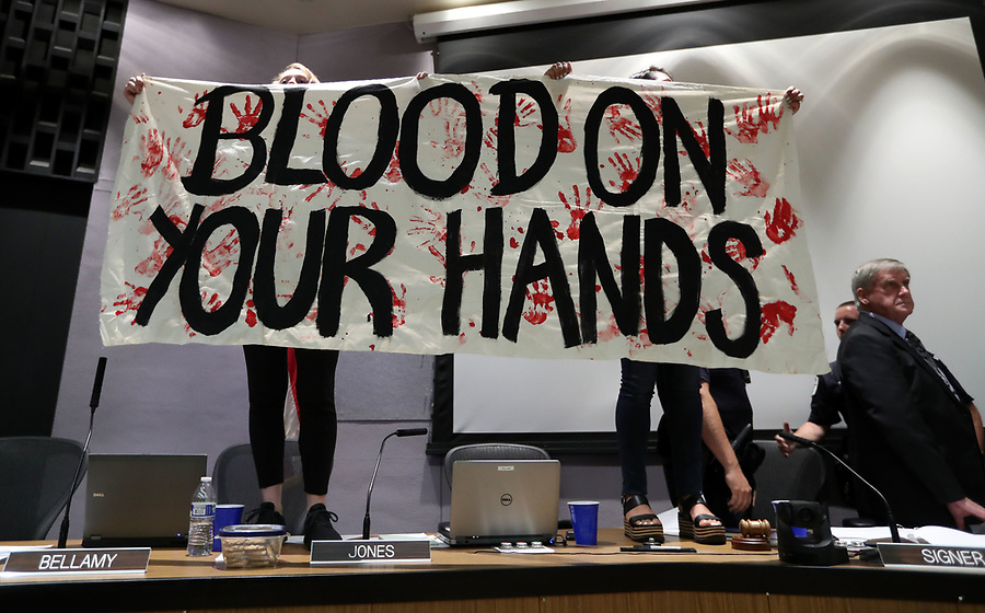 "Protestors hold a sign ""Blood on your hands"" as city council members exit behind during the Charlottesville City Council meeting Monday night in Charlottesville, Va. Photo/Andrew Shurtleff"