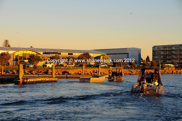 Boats waiting to be recovered at the Sulphur Point boat ramp in a winter setting sun over the Tauranga Harbour.