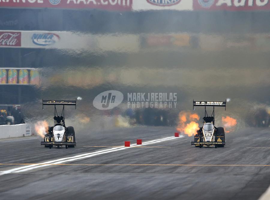 Feb 9, 2014; Pomona, CA, USA; NHRA top fuel dragster driver Khalid Albalooshi (left) races alongside Tony Schumacher during the Winternationals at Auto Club Raceway at Pomona. Mandatory Credit: Mark J. Rebilas-