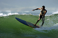 A local surfer rides a small wave in Tamarindo Costa Rica.