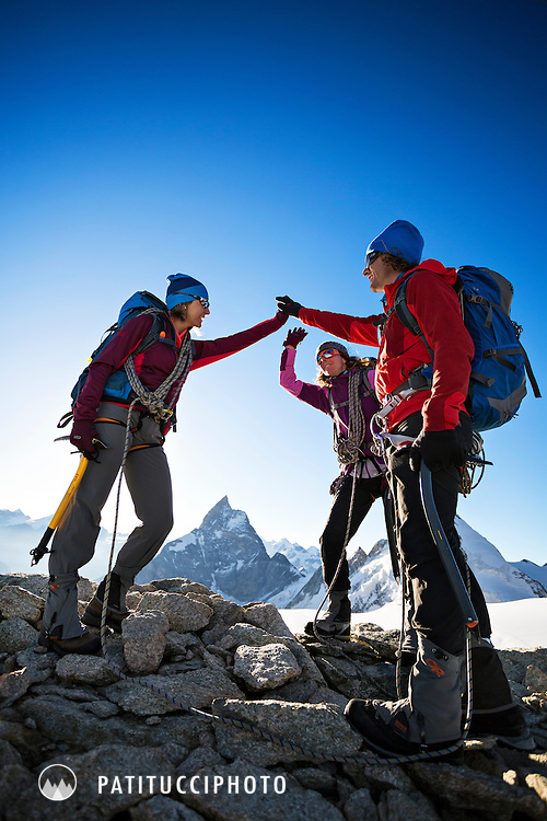 Three hikers high fiving and happy to be on the summit of the Tete Blanche, an easy peak on the fifth day of the Chamonix to Zermatt Glacier Haute Route that is the last climb before doing the big descent to Zermatt. In the distance is the Matterhorn.