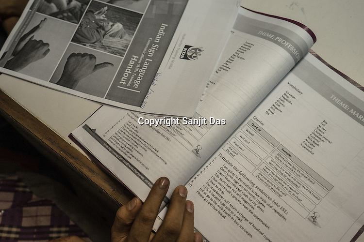 A deaf student reads the course books while attending classes at the Noida Deaf Society in Noida, Uttar Pradesh, India.