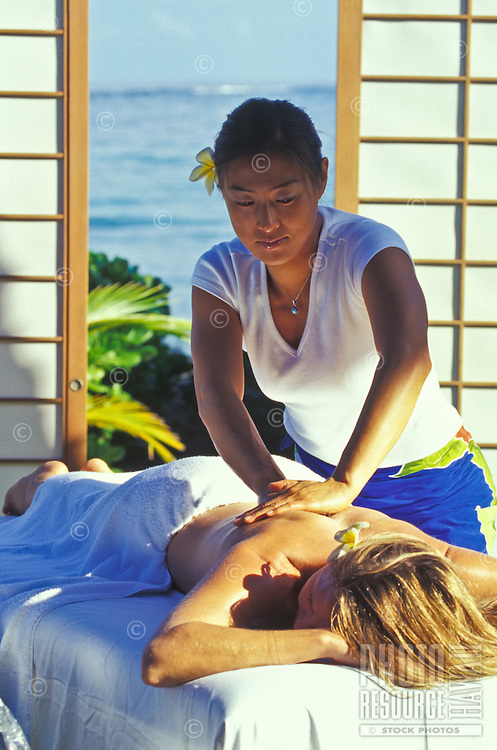Woman receiving a relaxing massage in a tropical setting