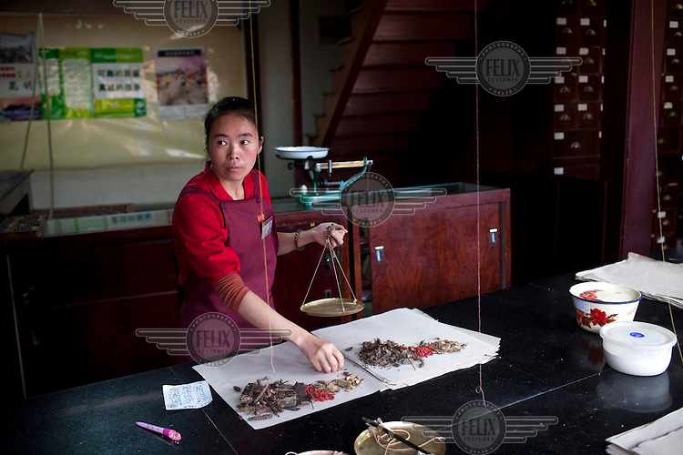 A woman measures ingredients in a Fu Lin Tang Traditional Chinese Medicine shop in Kunming.
