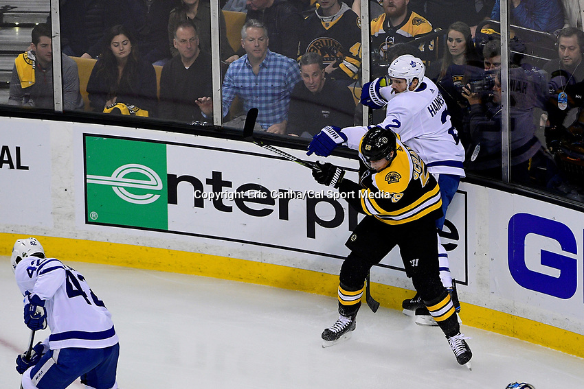 April 21, 2018: Boston Bruins center Tim Schaller (59) checks Toronto Maple Leafs defenseman Ron Hainsey (2) during game five of the first round of the National Hockey League's Eastern Conference Stanley Cup playoffs between the Toronto Maple Leafs and the Boston Bruins held at TD Garden, in Boston, Mass. Toronto defeats Boston 4-3, Boston leads Toronto 3 games to 2 in the best of 7 series.