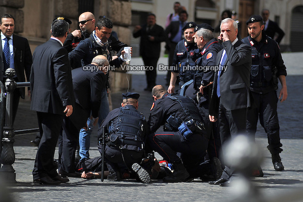 A Carabiniere police officer lies on the ground and is assisted by comrades after having been hit by a gun shot outside the Chigi Premier's office in Rome, Italy, on April 28, 2013. A second police officer was shot in the same attack, while the new government of Enrico Letta was being sworn in. The shooter was caught by Police soon after the attack.