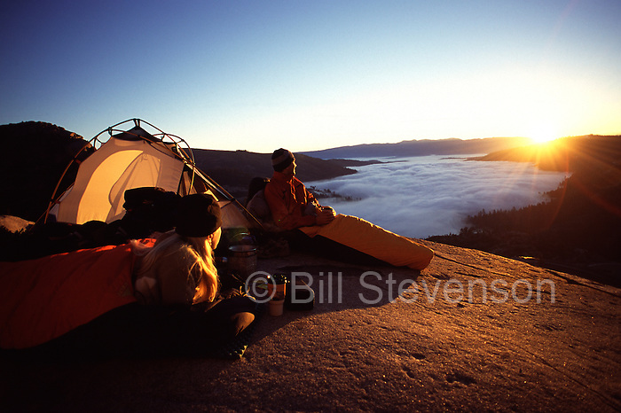 A picture of a couple watching the sunrise above a sea of clouds while camping above Donner Lake near Truckee, CA.