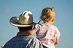 A young girl stands on her cowboy father's lap and watches the action at the  Minden Ranch Rodeo at the Douglas County Fairgrounds, Nev.