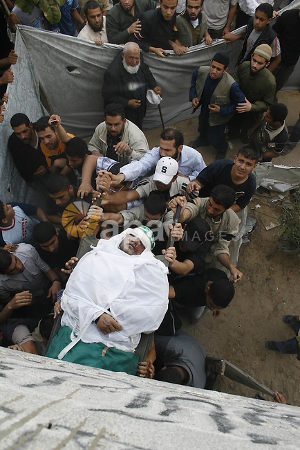 Palestinians carry the body of Hamas militant Ahmed Suleiman during his funeral in Rafah town in the southern Gaza Strip. Suleiman was one of four Hamas fighters who detonated two booby-trapped vehicles disguised as Israeli military jeeps at the Kerem Shalom border crossing used to deliver humanitarian supplies to Gaza yesterday wounding 13 Israeli soldiers.