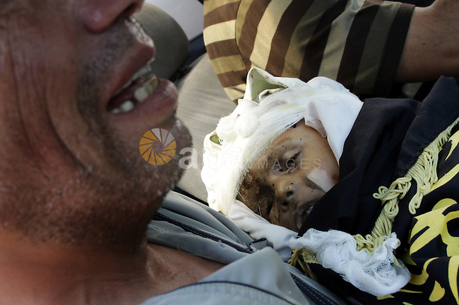 A Palestinian man carries the body of two-year-old boy Islam Qreqa during a funeral in Gaza City on August 20, 2011. Palestinians said at least nine militants have died in multiple Israeli strikes, as well as two children, one of them Islam Qreqa. Photo by Naaman Omar