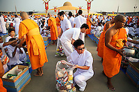 Buddhist monks receive alms from believers at the Wat Phra Dhammakaya temple in Pathum Thani province, north of Bangkok on Makha Bucha Day March 4, 2015. The Dhammakaya temple members include some of Thailand's most powerful politicians and is regarded as the country's richest Buddhist temple. Makha Bucha Day honours Buddha and his teachings, and falls on the full moon day of the third lunar month.  REUTERS/Damir Sagolj (THAILAND)