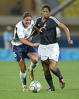23 August 2004:  Abby Wambach dribbles the ball away from Steffi Jones of Germany during the semifinal game at Pankritio Stadium in Heraklio, Greece.     USA defeated Germany, 2-1 in overtime.   Credit: Michael Pimentel / ISI