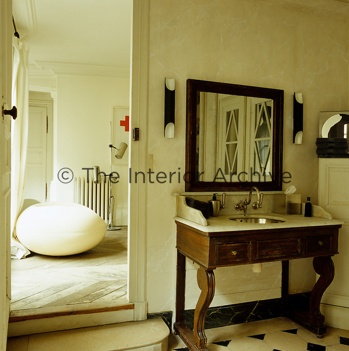 The bedroom opens into the bathroom furnished with a marble-topped wooden washstand