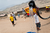 A Peruvian water distribution worker with a hose splashes drinking water from a truck into a plastic barrel on the dusty hillside of Pachacútec, a desert suburb of Lima, Peru, 22 January 2015. Although Latin America (as a whole) is blessed with an abundance of fresh water, having 20% of global water resources in the the Amazon Basin and the highest annual rainfall of any region in the world, an estimated 50-70 million Latin Americans (one-tenth of the continent's population) lack access to safe water and 100 million people have no access to any safe sanitation. Complicated geographical conditions (mainly on the Pacific coast), unregulated industrialization (causing environmental pollution) and massive urban poverty, combined with deep social inequality, have caused a severe water supply shortage in many Latin American regions.
