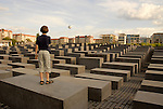 At the Jewish Memorial in Berlin, a child stands looking over the monuments to the sky above, and a hot air balloon drifting past.