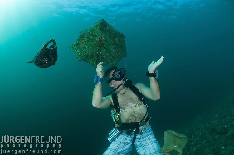 Clay Wideman clowning around with the trash collected underwater.