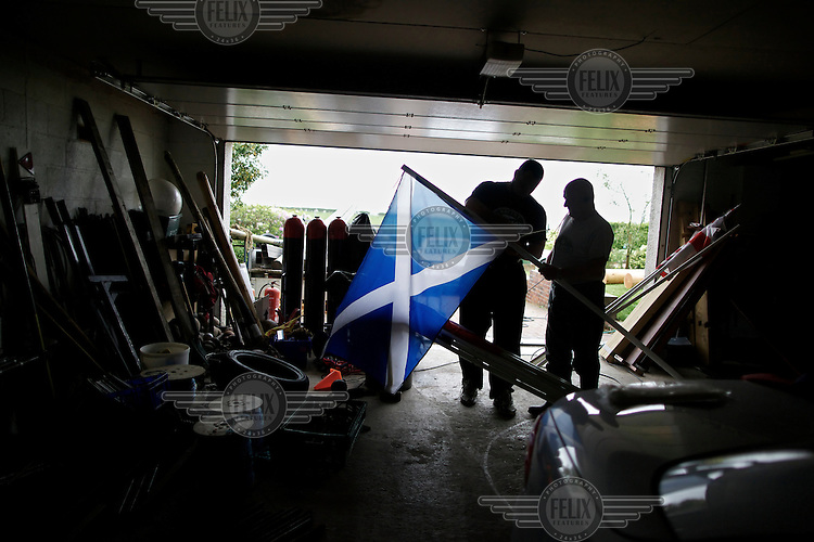 Gregor Edmunds from Scotland has been world caber tossing champon, No 1 Highland Games athlete in the world and World Highland Games champion 2007. Here he stands in a garage holding the national flag.