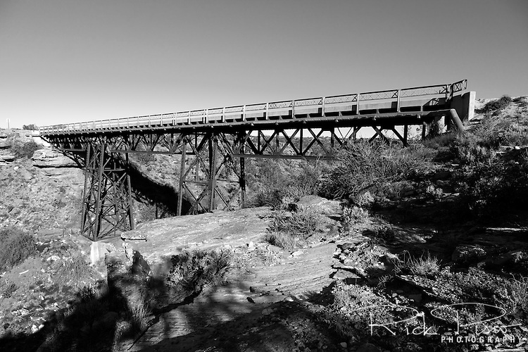 The Querino Canyon Bridge, located just outside of Houck, Arizona, was built in 1929 and spans Querino Canyon. The bridge is a truss design, 77 feet long, 20 feet wide, and comprised of a concrete-decked steel trestle with three Pratt deck trusses supported by steel piers.  Concrete abutments support the bridge from below and steel lattice guardrails line the roadway. The bridge and roadway became a county road in the 1960's after construction of Interstate 40 was completed and now carries local traffic on the Navajo Indian Reservation. The bridge was listed in the National Register of Historic Places in 1988.